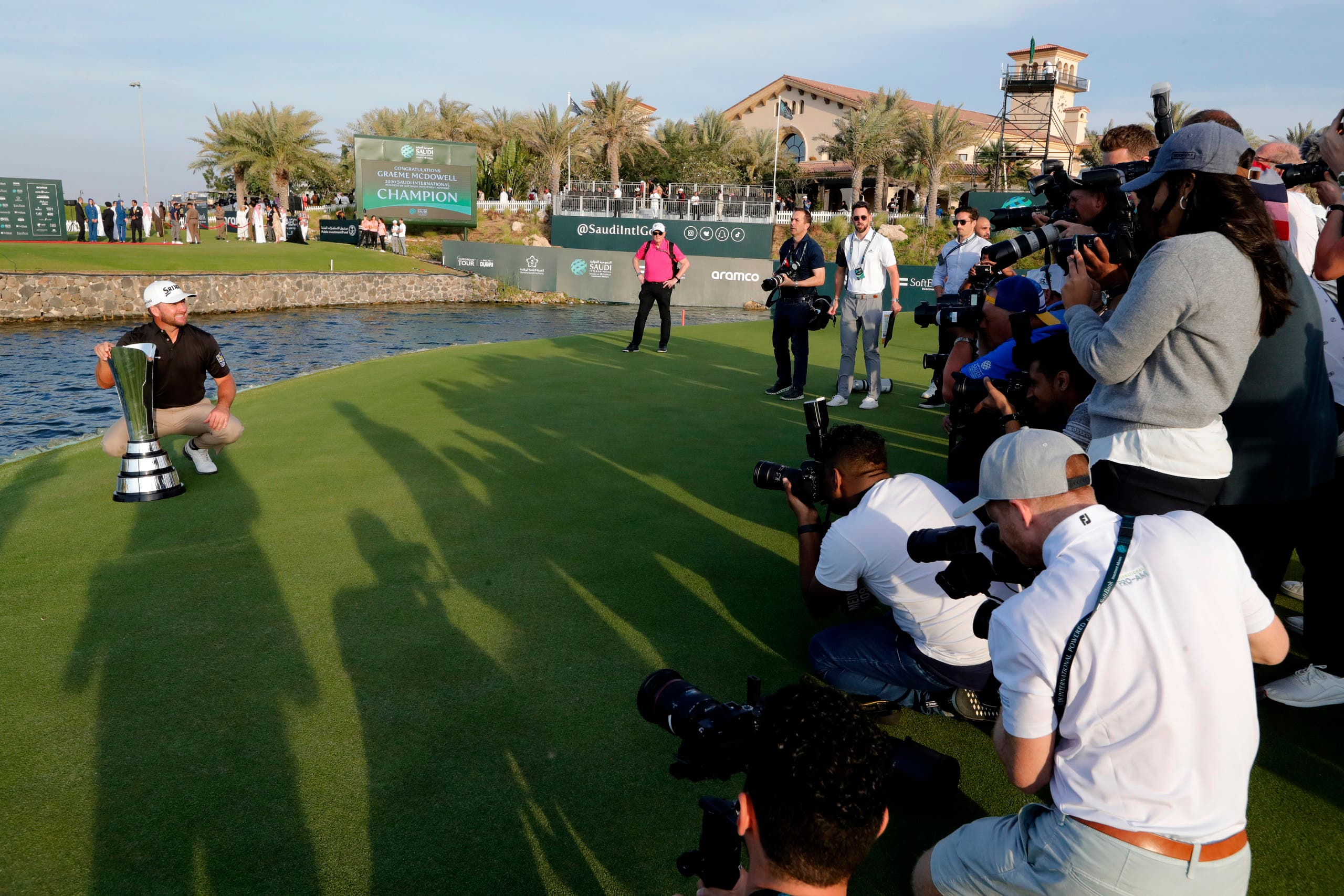Cameramen film Graeme McDowell from Northern Ireland as he celebrates the trophy after he wins the final round of the Saudi International at Royal Greens Golf and Country Club on Feb. 2, 2020. (AP)
