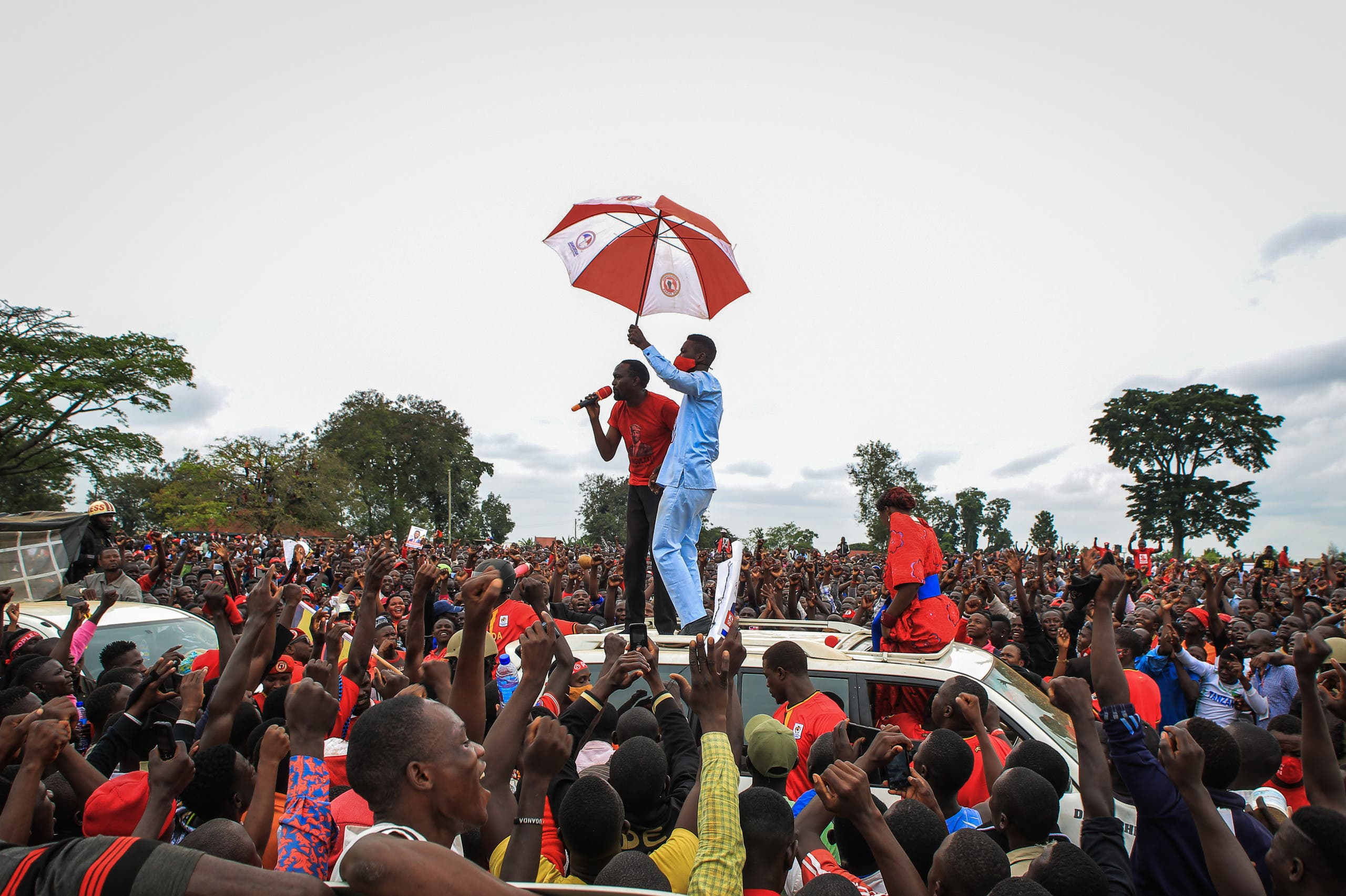 Ugandan musician turned politician Robert Kyagulanyi (C), also known as Bobi Wine, holds an umbrella as he was introduced to supporters during his presidential rally before he got arrested in Luuka, Uganda. (AFP)