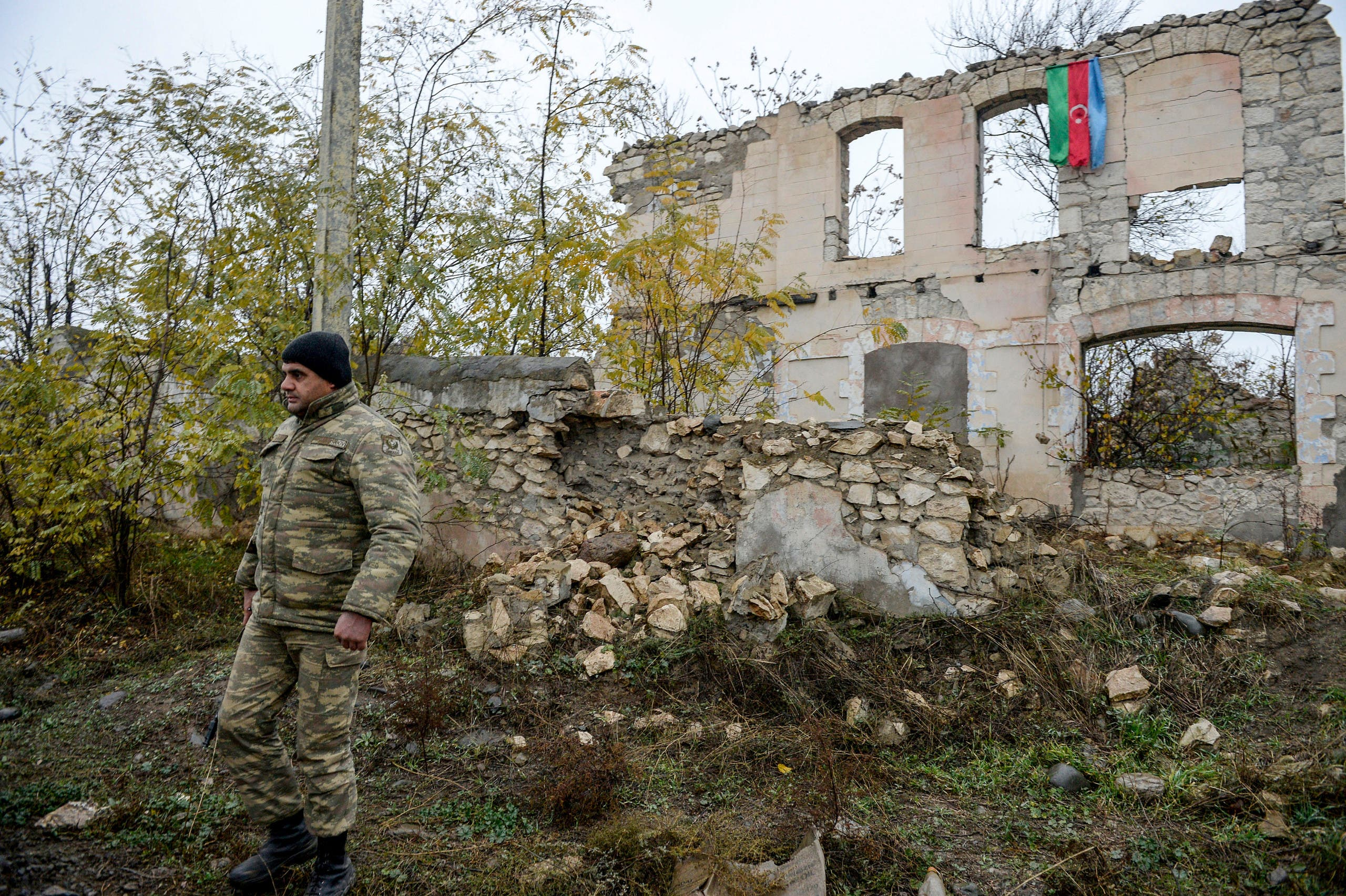 An Azerbaijani soldier walks near a destroyed house on the outskirts of the town of Fuzuli on November 18, 2020. (AFP)