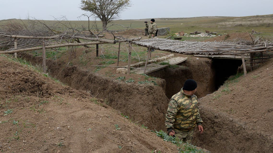 An Azerbaijani soldier walks in a trench of an enemy defensive structure outside the town of Fuzuli on November 18, 2020. As part of the deal, Armenia and Nagorno-Karabakh must return the Aghdam, Kalbajar and Lachin districts to Azerbaijan starting on November 20, with a completion deadline of December 1.