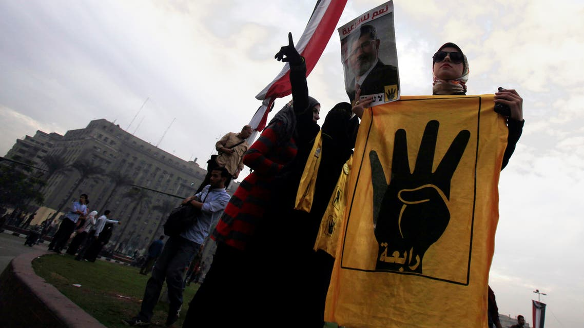 Pro-Mursi university students and supporters of the Muslim Brotherhood display a poster of ousted President Mohamed Mursi at Tahrir Square in Cairo December 1, 2013. (Reuters)