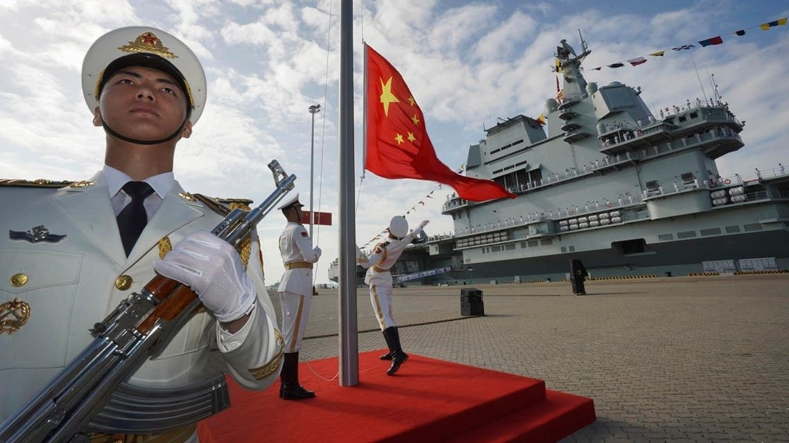 In this photo taken December 17, 2019, the Chinese flag is raised during the commissioning ceremony of China's Shandong aircraft carrier at a naval port in Sanya, south China's Hainan Province. (AP)