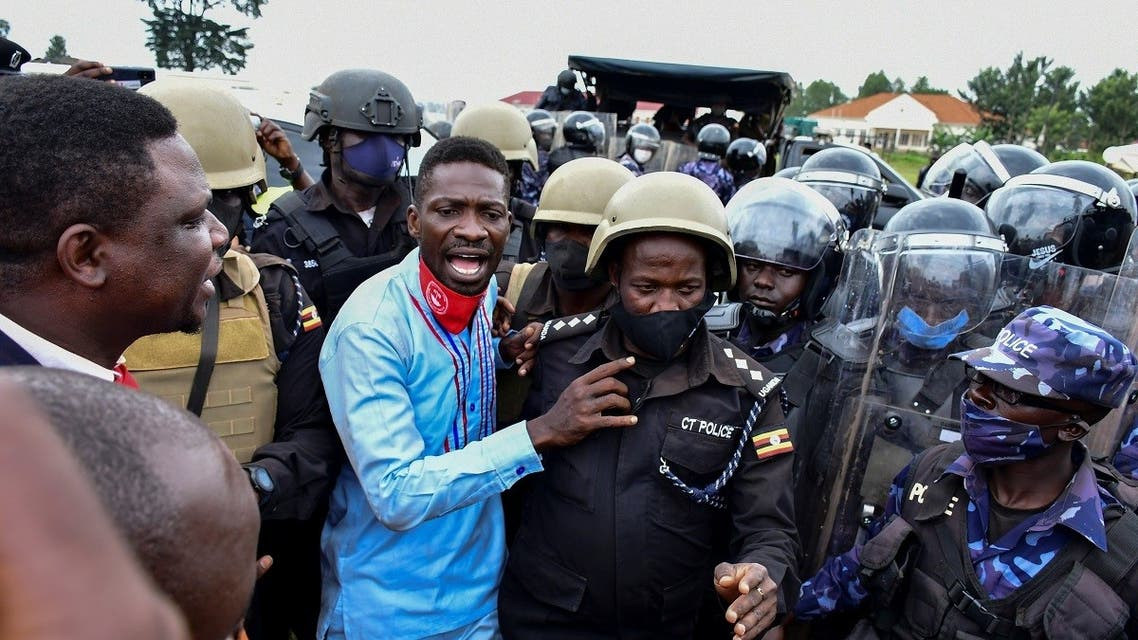 Ugandan presidential candidate Robert Kyagulanyi also known as Bobi Wine is led into a vehicle by riot policemen in Luuka district, eastern Uganda, on November 18, 2020. (Reuters)