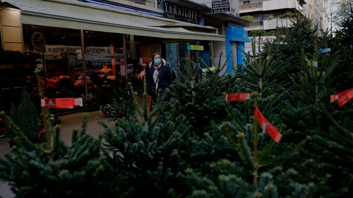 A woman watches christmas trees in a florist, in Paris, on November 20, 2020. (AP)