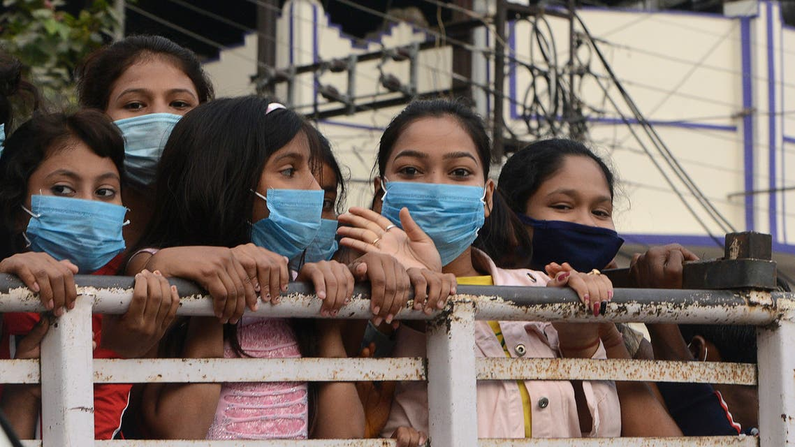 People wear face masks as they stand along a sidewalk in Siliguri on November 20, 2020. (AFP)
