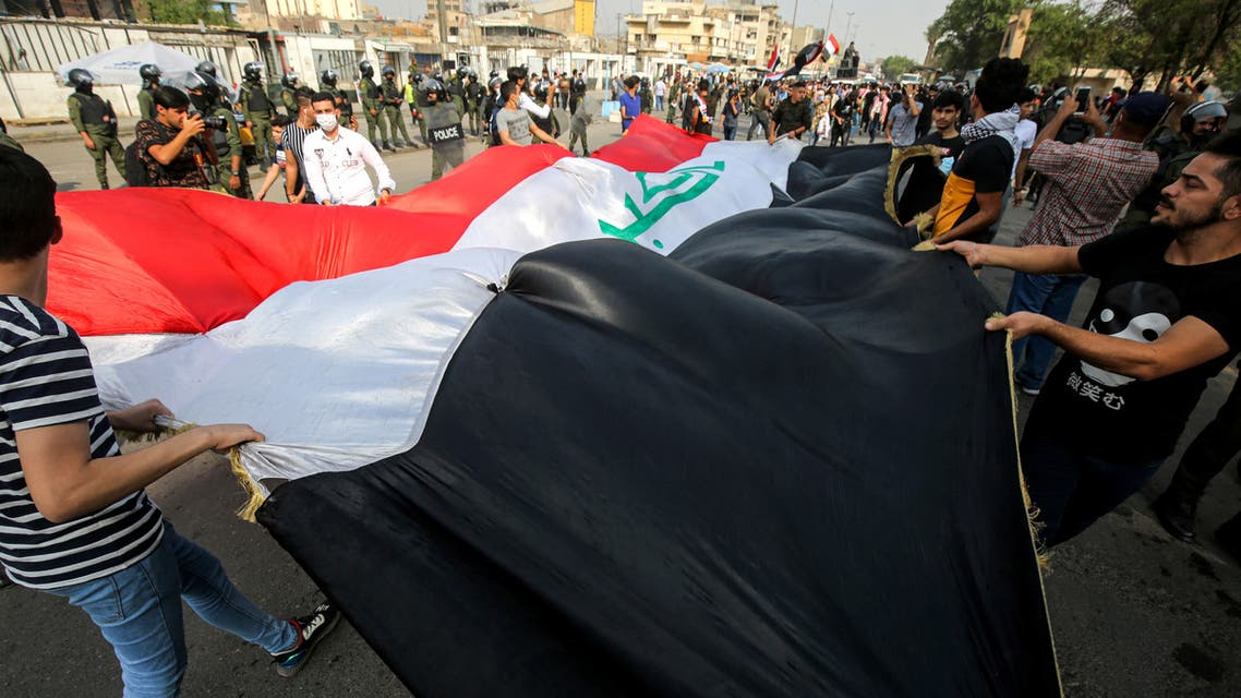 Demonstrators wave together a giant Iraqi national flag during an anti-government protest over corruption and poor services in Tahrir Square in the centre of Iraq's capital Baghdad on November 8, 2020.