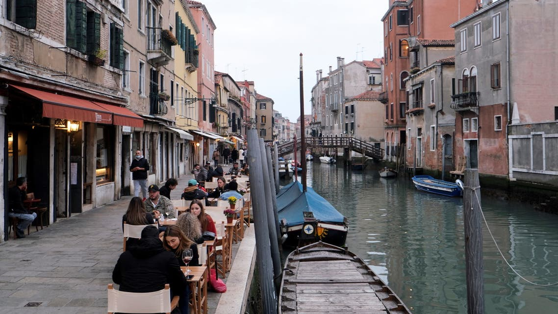People sit at tables along the canal, as the number of people infected by the coronavirus disease (COVID-19) continues to rise, in Venice, Italy, November 14, 2020. REUTERS/Manuel Silvestri