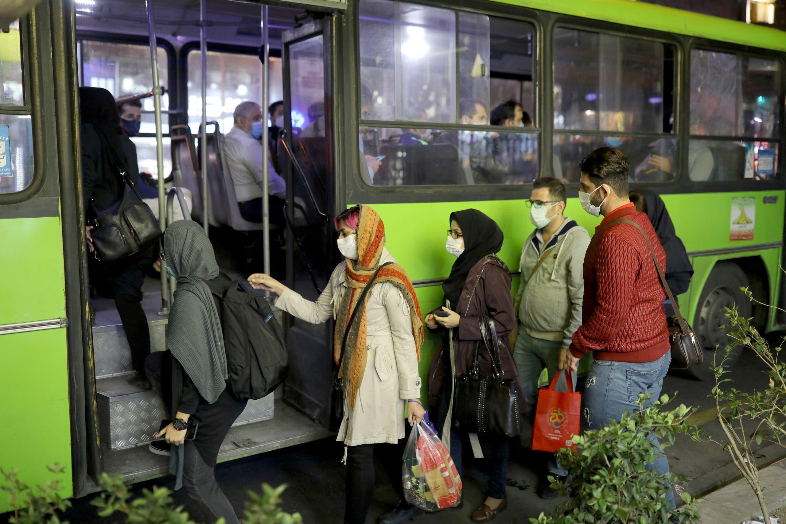 سكان في طهران يرتدون الكمامات للوقاية من كورونا خلال ركوبهم الباص