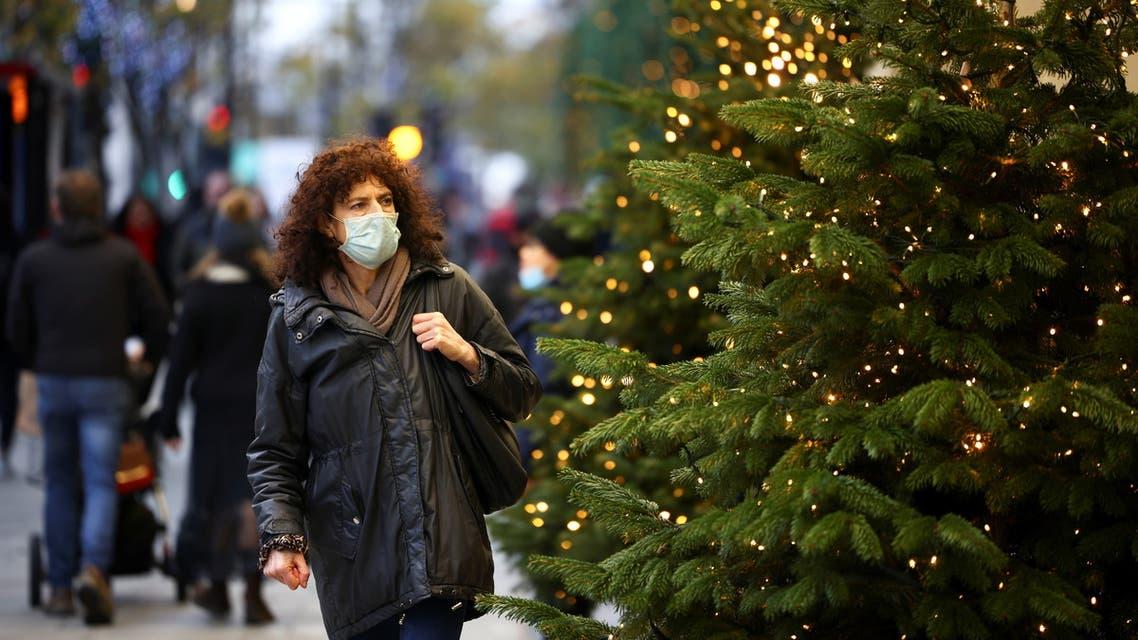 A woman walks past Christmas trees on Oxford Street, amid the coronavirus disease (COVID-19) outbreak, in London, Britain, November 21, 2020. (Reuters)