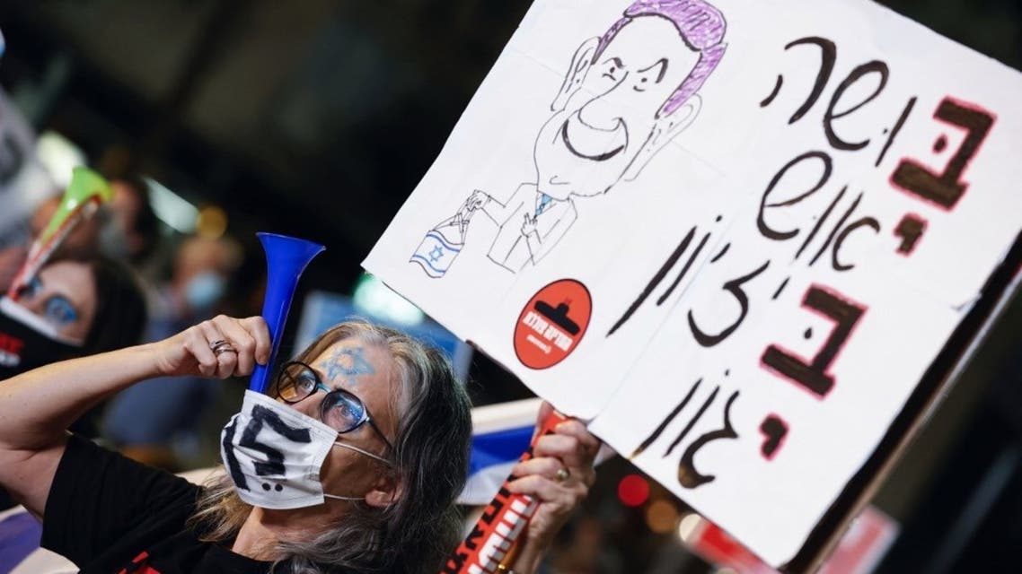 An Israeli protester wearing a protective mask due to the COVID-19 pandemic, lifts a placard as she blows a plastic horn during a demonstration against Prime Minister Benjamin Netanyahu. (AFP)