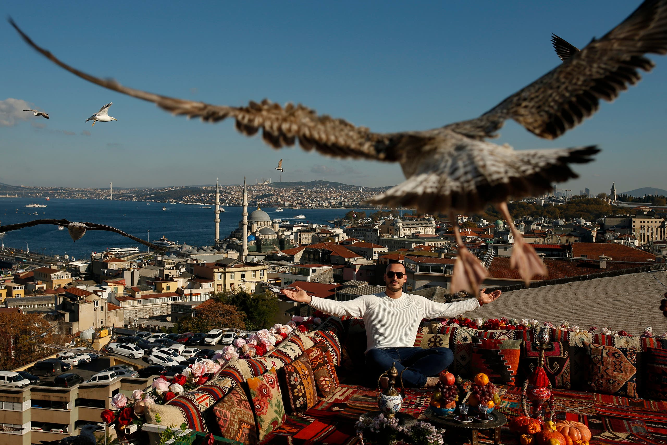 A seagull files over a man sitting at a coffee shop backdropped by the Bosporus Strait in Istanbul on Nov. 17, 2020. (AP)