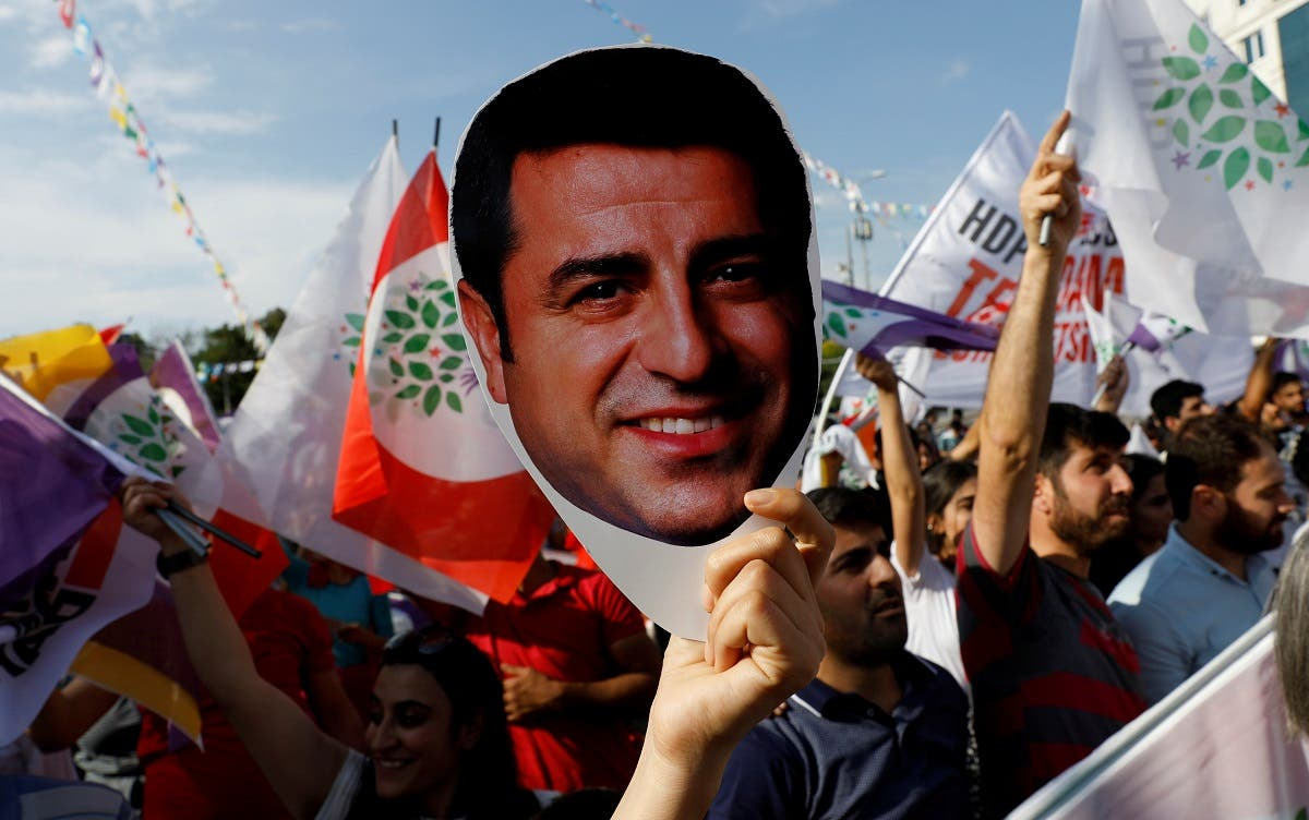 A supporter of Turkey's main pro-Kurdish Peoples' Democratic Party (HDP) holds a mask of their jailed former leader and presidential candidate Selahattin Demirtas during a rally in Ankara, Turkey, June 19, 2018. (Reuters/Umit Bektas)