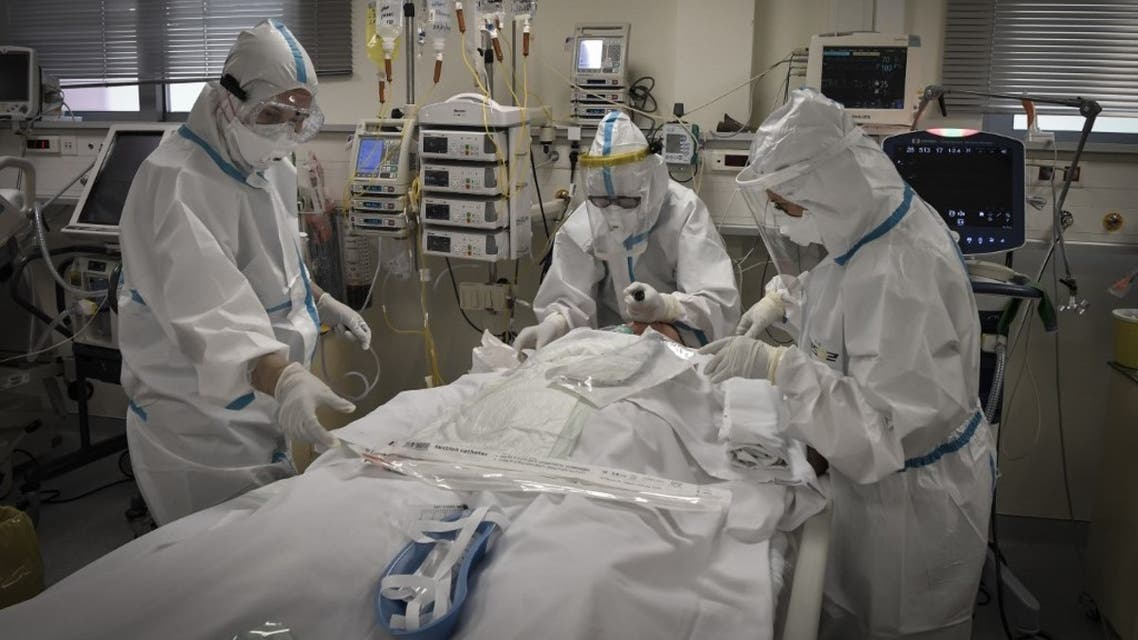 Nurses attend to a patient suffering form the novel coronavirus, Covid-19, in the Intensive Care Unit (ICU) at the Voula (Asklepeion) hospital located in an Athens' southern suburb on November 20, 2020.  (AFP)