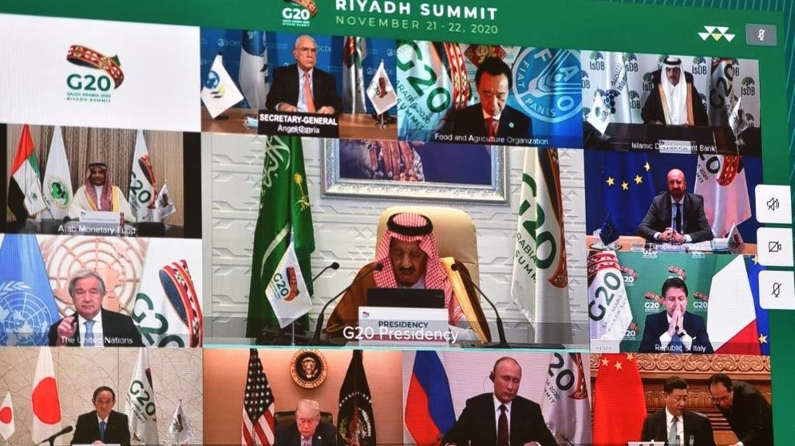 Displayed on a projected screen at the International Media Centre in Saudi Arabia's capital Riyadh on November 21, 2020, Saudi King Salman bin Abdulaziz gives an address opening the G20 summit, held virtually, while surrounding him are other G20-participating leaders. (AFP)