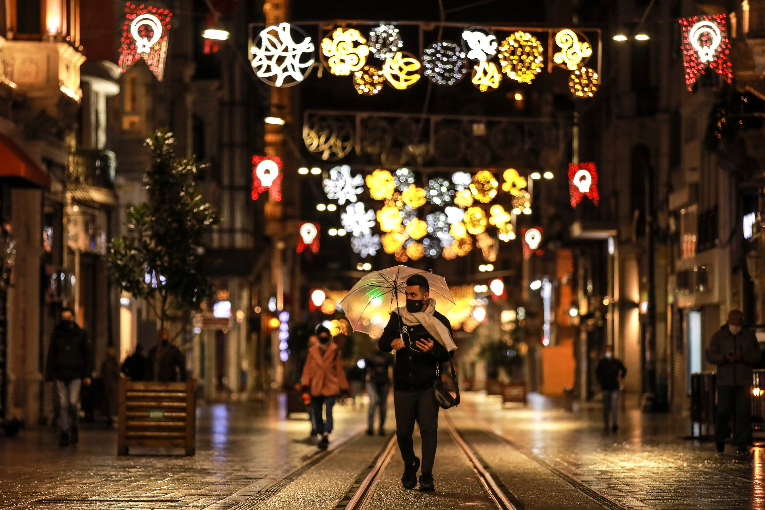 A few people walk in Istiklal street, the main shopping street in Istanbul, minutes into the lockdown, part of the new measures to try curb the spread of the coronavirus, Saturday, Nov. 21, 2020. (AP)