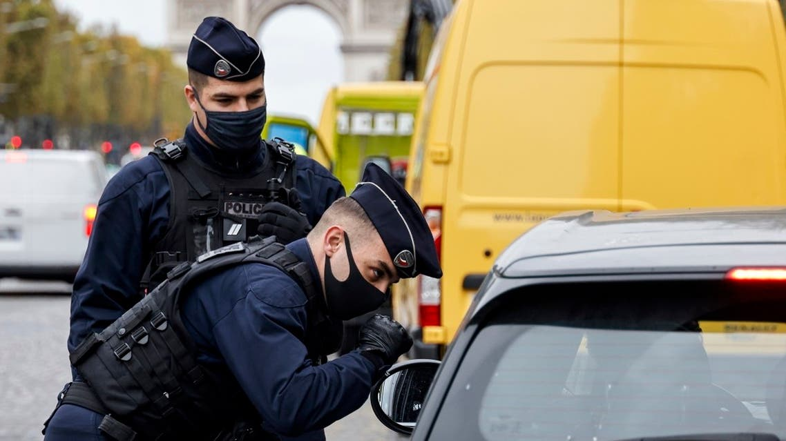 French police officers control a car on the Champs-Elysee avenue in Paris, on October 30, 2020, on the first day of a second national lockdown to curb the spread of coronavirus. (Thomas Coex/AFP)