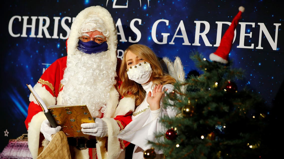 A man dressed as Santa Claus and woman dressed as angel wear face masks ahead of a news conference to introduce the upcoming Christmas Garden event of iluminated objects at a botanic garden, amid the coronavirus outbreak, in Berlin, Germany. (Reuters)