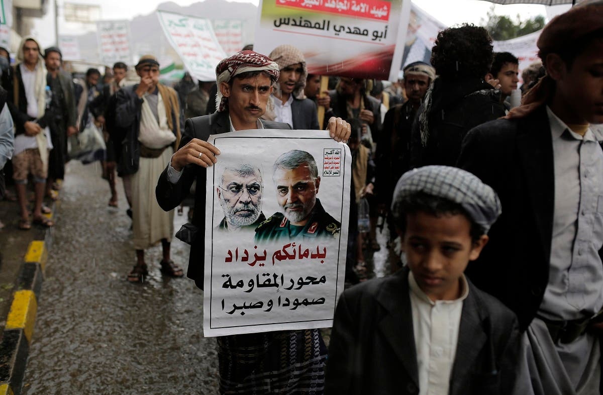 A Yemeni Shia Houthi holds a poster of Iraqi militia commander Abu Mahdi al-Muhandis and Iranian military commander Qassem Soleimani during a protest in Sanaa, Yemen, Jan. 6, 2020. (AP)