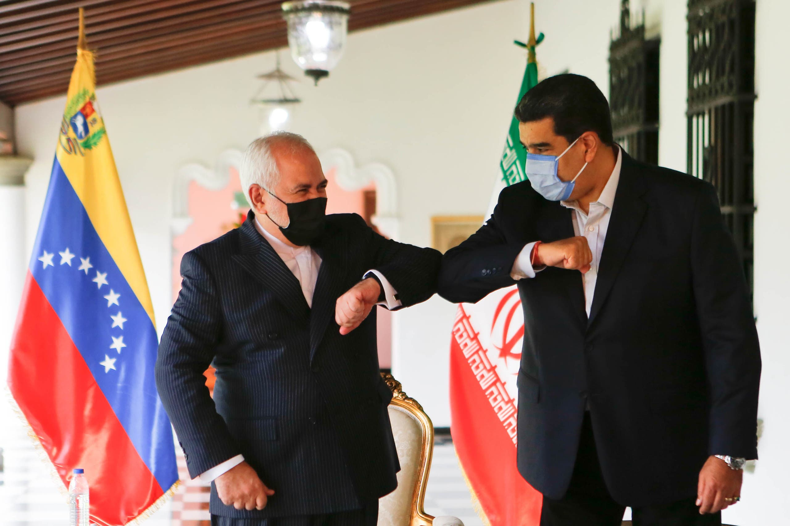 Venezuela's President Nicolas Maduro (R) bumping elbows with the Foreign Minister of the Islamic Republic of Iran, Javad Zarif (L) at Miraflores Palace in Caracas, on November 5, 2020. (File photo: AFP)