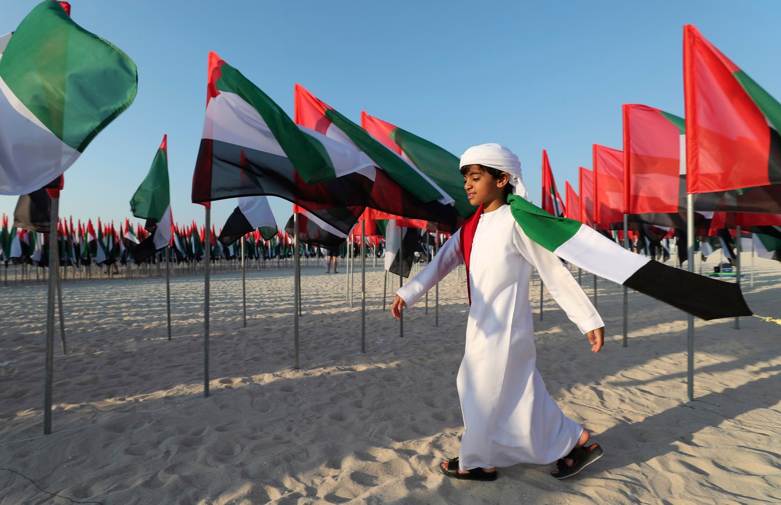 An Emirati boy walks among UAE national flags set up to celebrate the country's Flag Day in Dubai on Nov. 3, 2020. (AP)