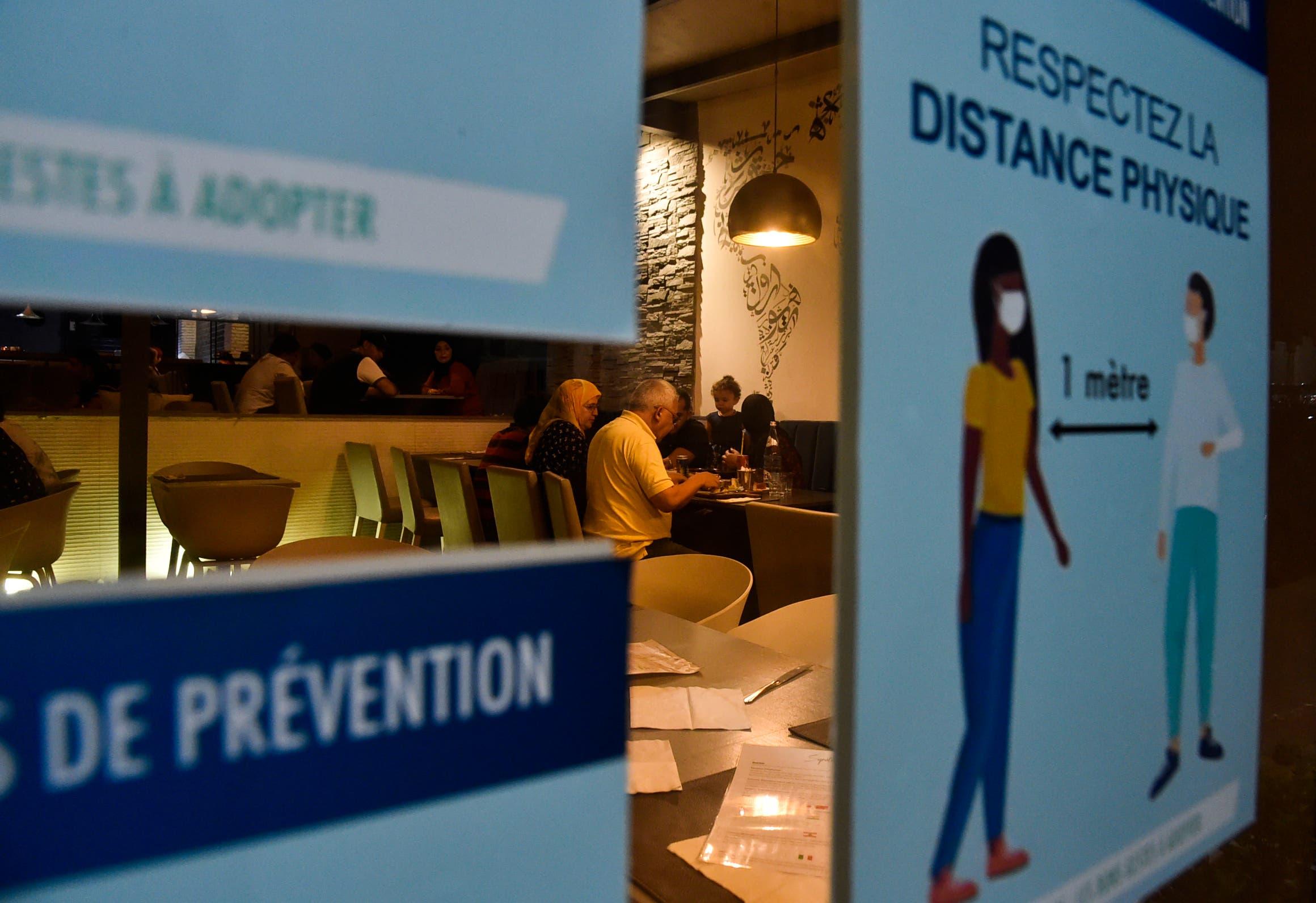 ملصق يحث على احترام التباعد للوقاية من كورونا على مدخل أحد مطاعم بالجزئر