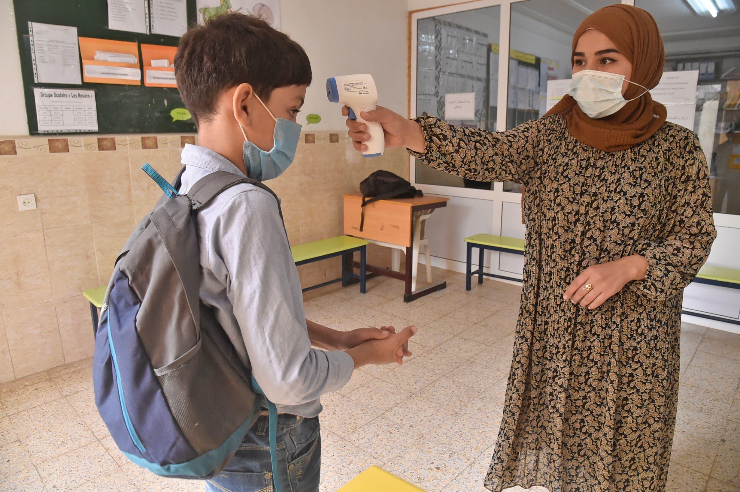 قياس حرارة الطلاب والتزام بالكمامات للوقية من كورونا في إحدى مدارس الجزاير