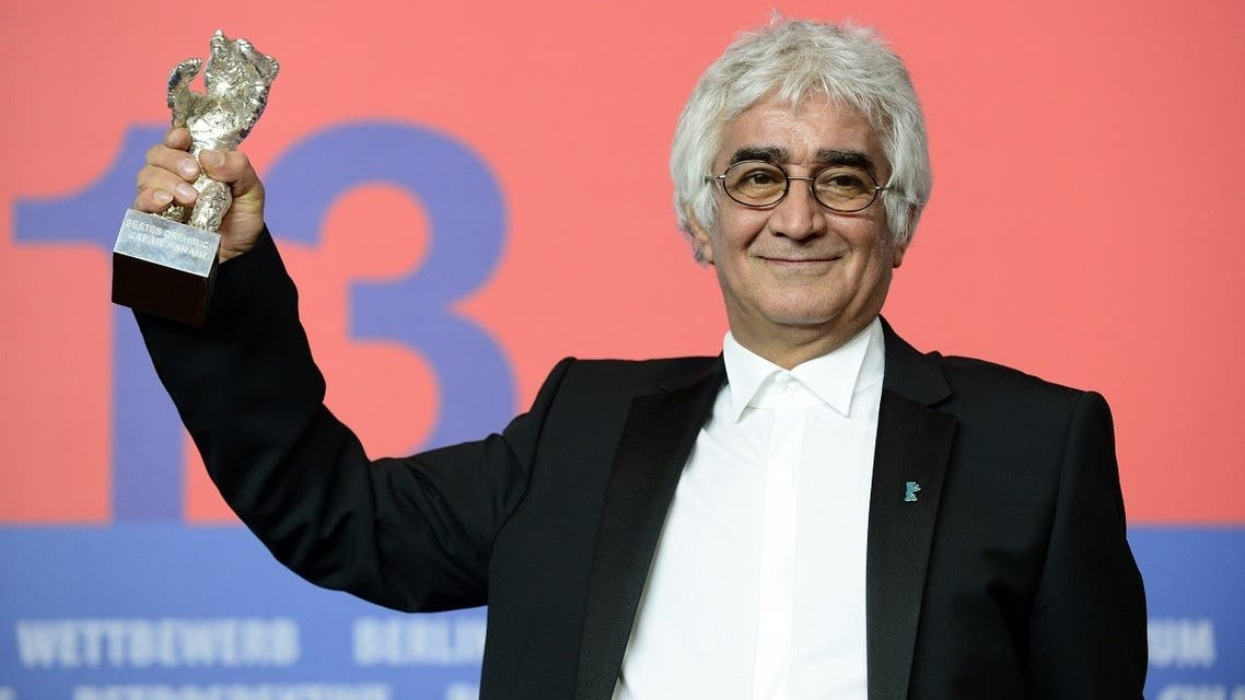"""In this file photo taken on February 16, 2013, Iranian director Kambuzia Partovi holds his Silver Bear for Best Script award he received in place of Jafar Panahi (not pictured) for the movie """"Parde"""" (Closed Curtain) during a press conference following the 63rd Berlinale awards ceremony in Berlin. (John MacDougall/AFP)"""