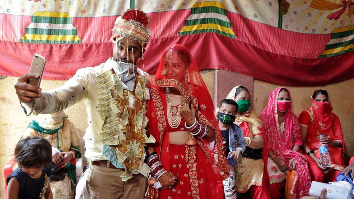 Couple Sachin Chandaliya and SonIya Bohat take a selfie after getting married at a marriage bureau at Bandra in Mumbai, India, Monday, June 15, 2020. (AP)