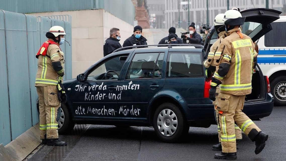 """Firefighters remove the car which crashed into the gate of the main entrance of the chancellery in Berlin, the office of German Chancellor Angela Merkel in Berlin, Germany, on November 25, 2020. Letters written on the car read: """"You damn killers of children and old people."""" (Reuters)"""