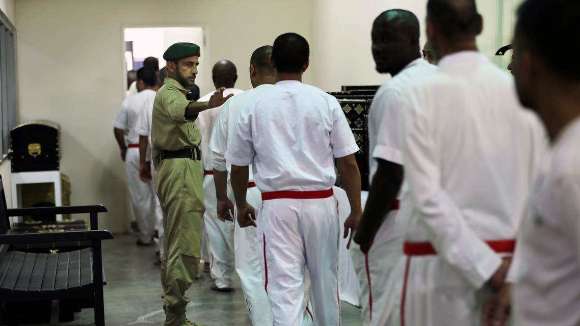 A policeman directs prisoners leaving their daily shift at the Inmates Education and Training Department of the Central Prison in Dubai on July 26, 2017. (AP)