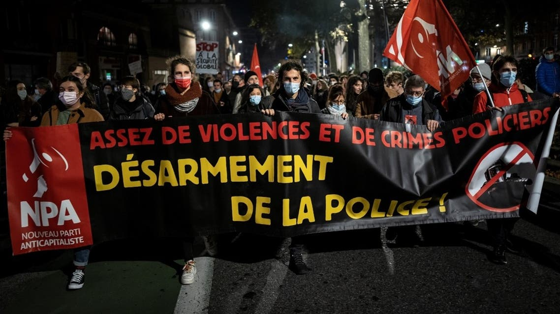 "People hold a banner reading ""enough violence and police crimes, disarm the police"" as they take part in a demonstration, on November 26, 2020, in Toulouse, southern France. (Lionel Bonaventure/AFP)"