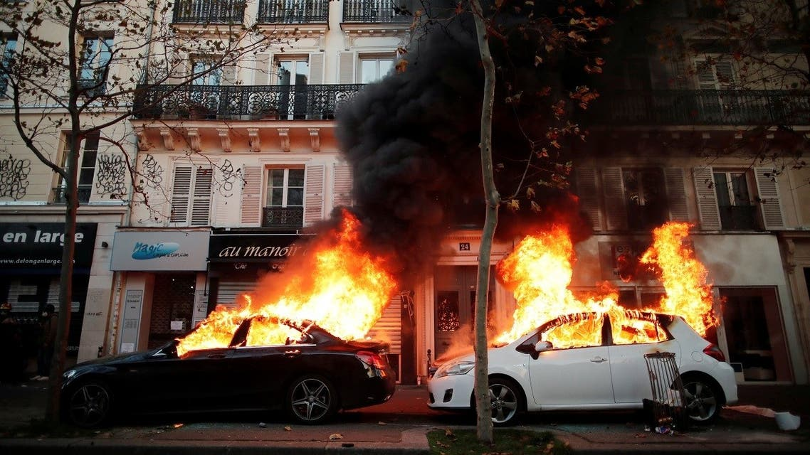 """Cars burn during a demonstration against the """"Global Security Bill"""" in Paris, November 28, 2020. (Reuters/Benoit Tessier)"""