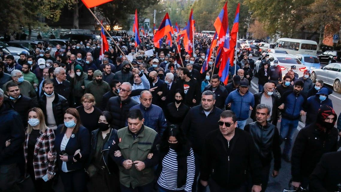 Protesters with Armenian flags walk along a street during a protest against an agreement to halt fighting over the Nagorno-Karabakh region, in Yerevan, Armenia, Thursday, Nov. 12, 2020. (AP/Dmitri Lovetsky)