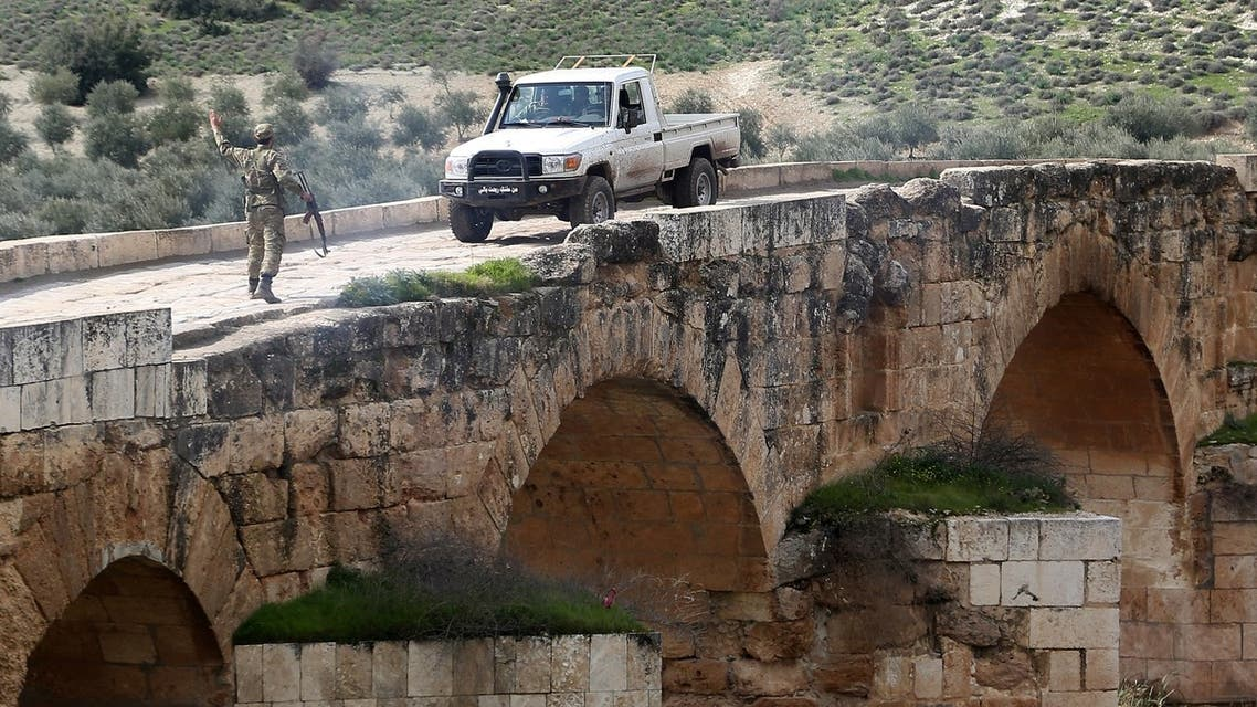 A Turkish-backed Syrian opposition fighter gestures to an incoming pickup truck driving on the Roman bridge in the archaeological site of Cyrrhus, or Nabi Huri, northeast of the Syrian city of Afrin, after they took control of the area from the Kurdish People's Protection Units (YPG) on February 23, 2018.