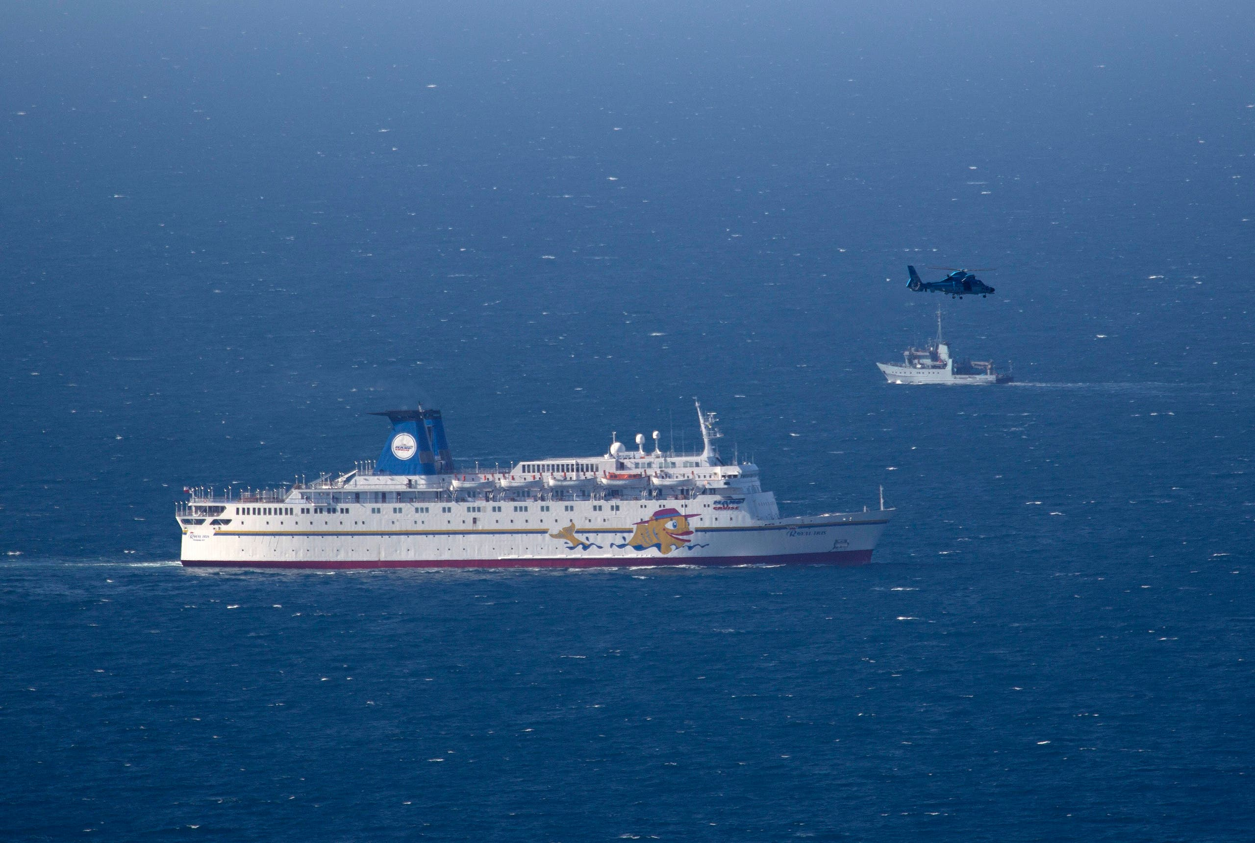 An Israeli military naval ship and an Israeli air force helicopter operate next to a cruise ship off the coast of Haifa on April 25, 2013. (AP)