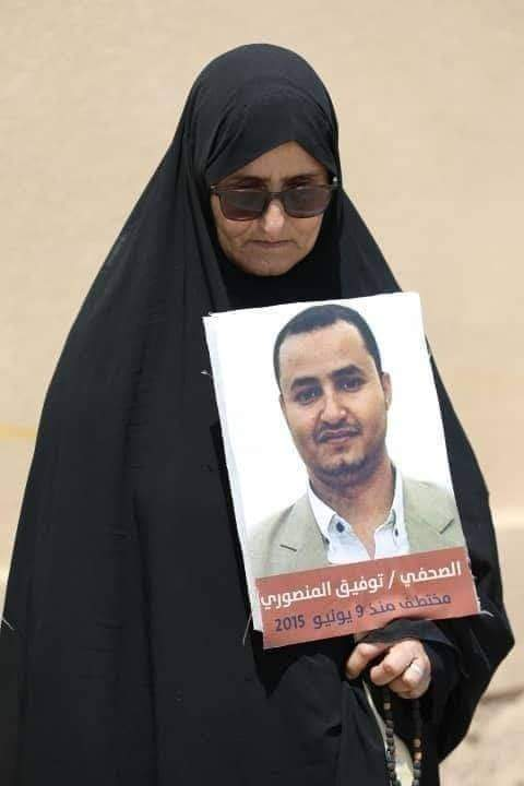 والدة الصحافي المنصوري وهي تحمل صورة ابنها المختطف