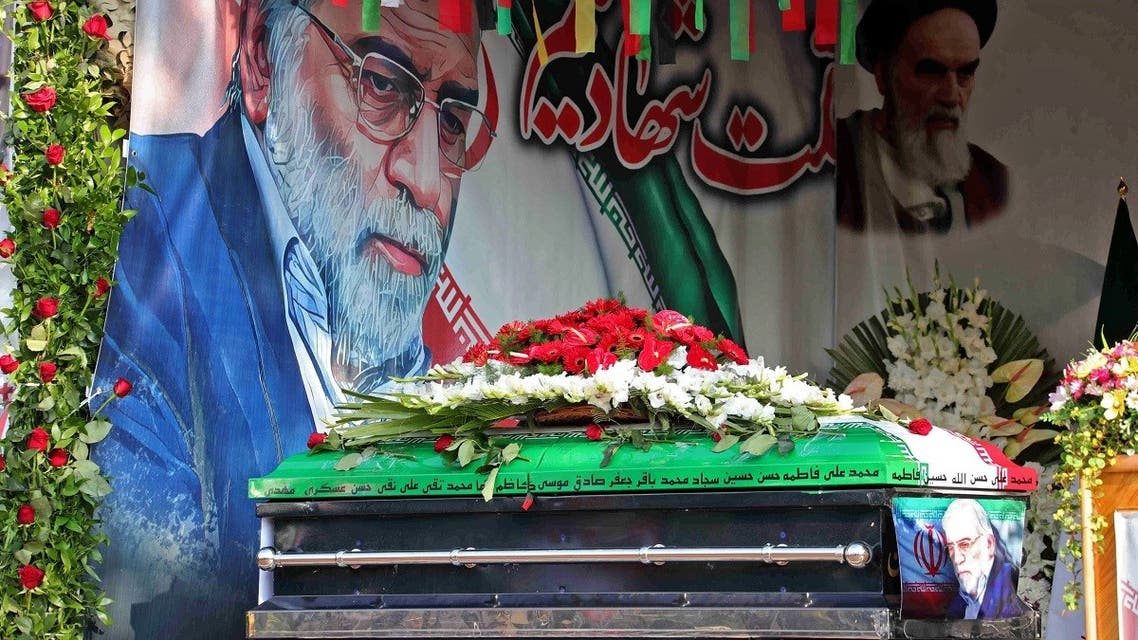 A handout picture provided by Iran's Defense Ministry on November 30, 2020 shows the coffin of slain top nuclear scientist Mohsen Fakhrizadeh in front of a large display depicting Fakhrizadeh next to Iran's supreme leader Ayatollah Ali Khamenei during the funeral ceremony in Tehran. (AFP)