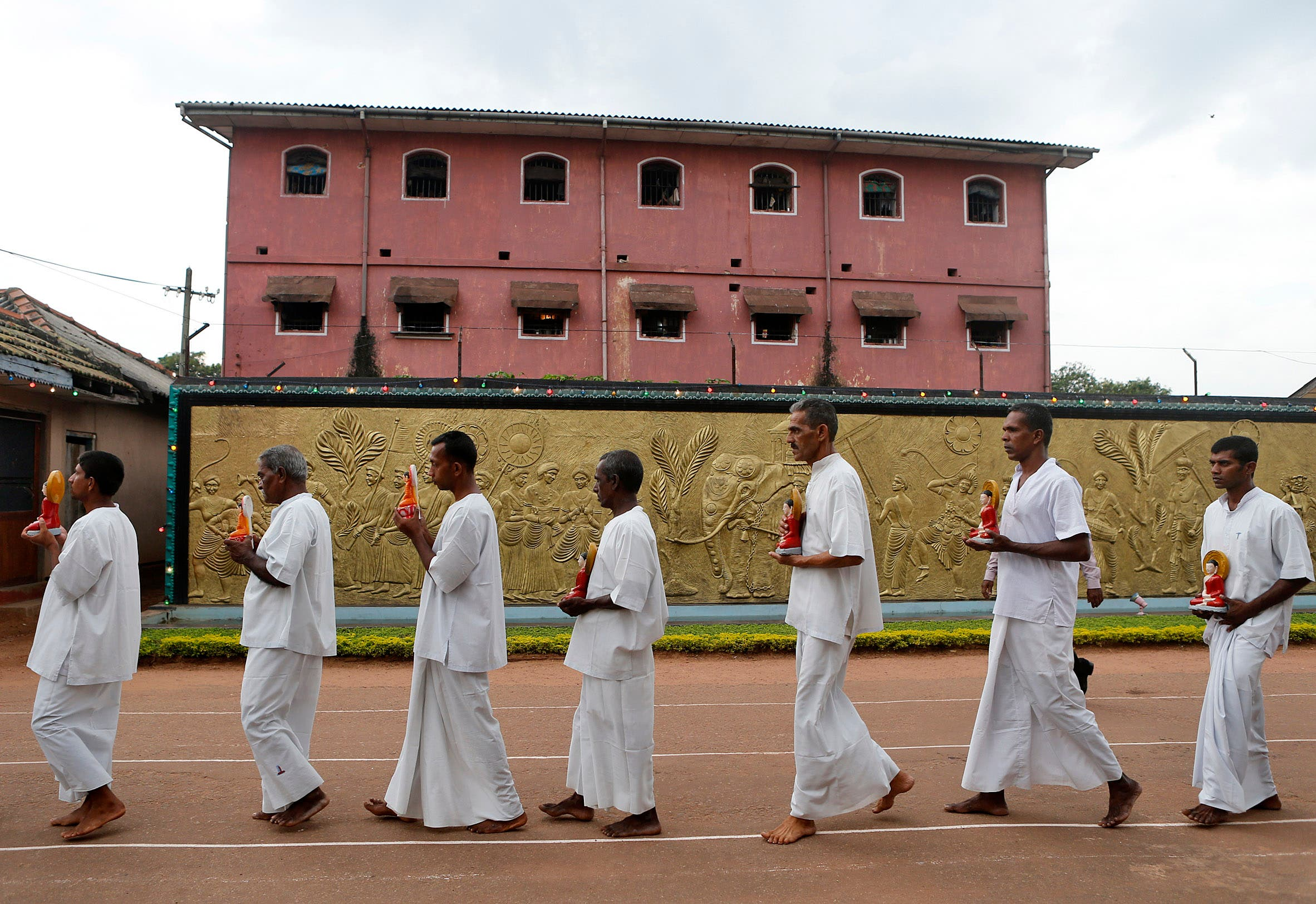 Sri Lankan inmates of the Welikada prison carry statues of Lord Buddha as they take part in a religious ceremony on the eve of new year on Monday, Dec. 31, 2012 (AP)