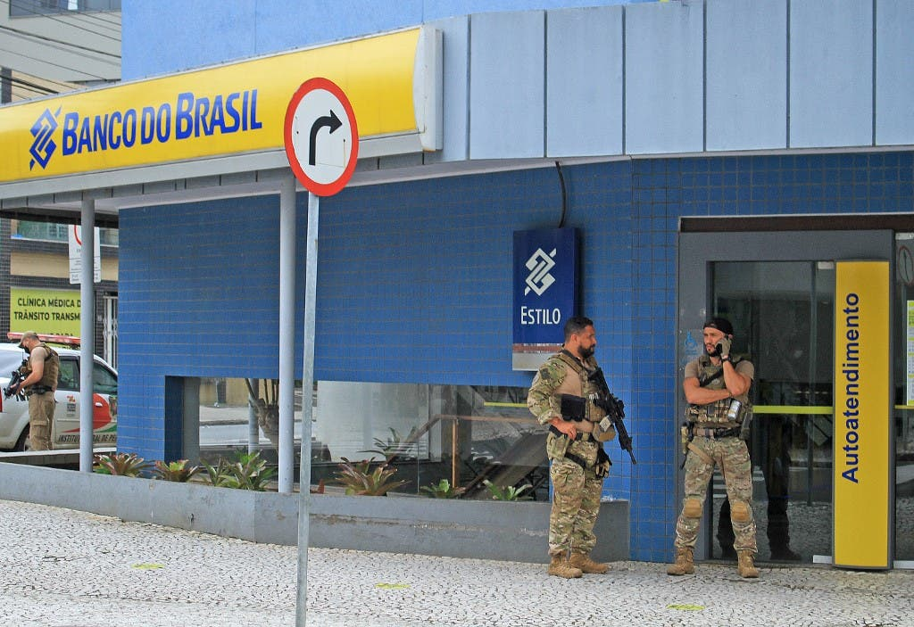 Police officers stand guard outside the bank which robbers struck just after midnight, in Criciuma, Brazil, on December 1, 2020. (Guilherme Haun/AFP)
