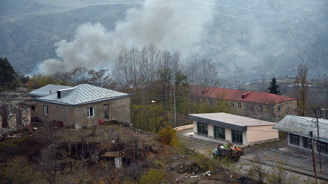 A truck loaded with firewood and other items is seen on a road in the town of Lachin (called Berdzor by the Armenians) as smoke rises from a burning house set on fire by departing residents on November 30, 2020. Armenia is to hand back the Lachin district to Azerbaijan by December 1 as part of a peace deal that ended six weeks of fighting over the breakaway region of Nagorno-Karabakh.