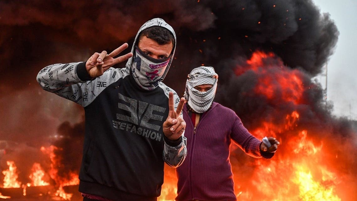 Masked protesters flash the victory gesture while standing by a fire during an anti-government demonstration in Habboubi square in the center of Iraq's southern city of Nasiriyah in Dhi Qar province on November 29, 2020. (Asaad Niazi/AFP)