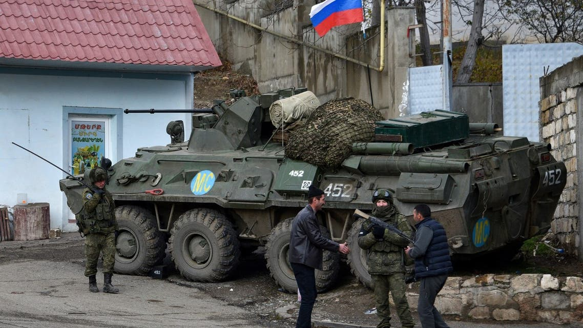 Men interact with a Russian peacekeeper in the town of Lachin (called Berdzor by the Armenians) on November 30, 2020. Armenia is to hand back the Lachin district to Azerbaijan by December 1 as part of a peace deal that ended six weeks of fighting over the breakaway region of Nagorno-Karabakh. (AFP)
