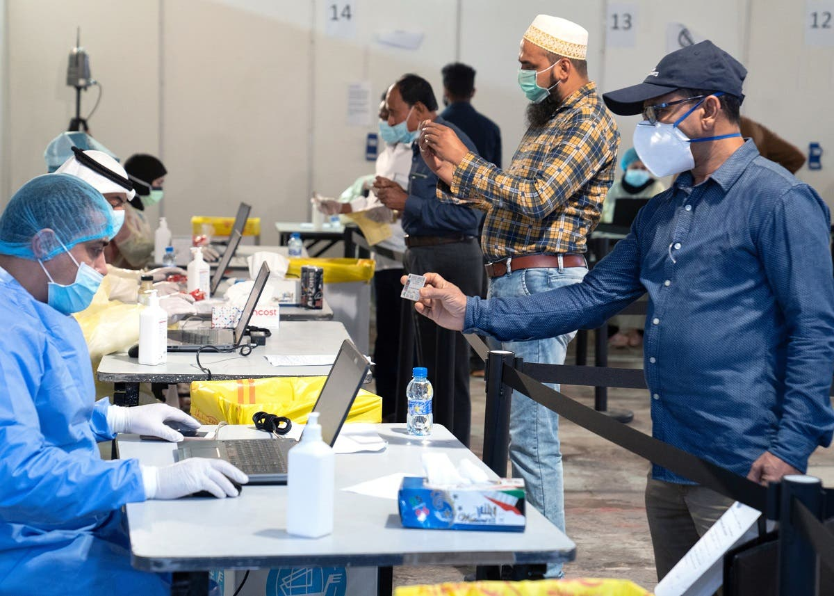 Expatriates, arriving to Kuwait, stand a safe distance apart to give their details to ministry of health officials in a makeshift coronavirus testing centre. (File photo: Reuters)