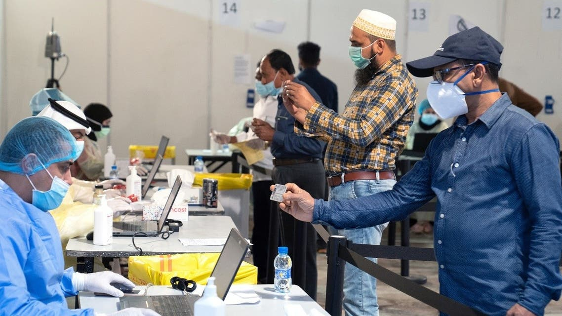 Expatriates, arriving to Kuwait, stand a safe distance apart to give their details to ministry of health officials in a makeshift coronavirus testing centre, at Kuwait International Fairgrounds in Mishref, Kuwait March 18, 2020. (Reuters/Stephanie McGehee)