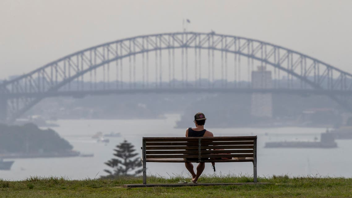 A man watches the sunset from a park bench in the Eastern suburbs of Sydney, Australia, Monday, Nov. 16, 2020. (AP)