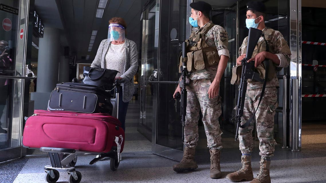 Lebanese soldiers stand guard as a woman leaves the Rafik Hariri International Airport in Beirut, Lebanon, July 1, 2020. (AP)