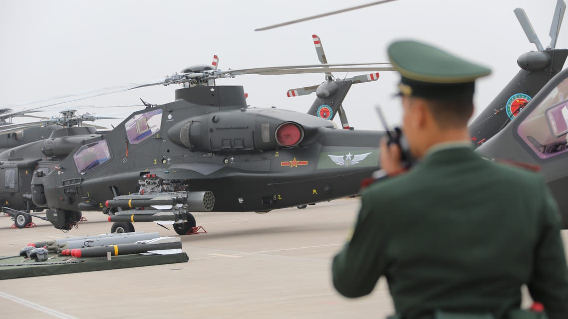A military personnel speaks on his walkie-talkie before a military helicopter from Chinese People's Liberation Army (PLA) Air Force during the China Helicopter Exposition in Tianjin, China October 10, 2019. Picture taken October 10, 2019. REUTERS/Stringer ATTENTION EDITORS - THIS IMAGE WAS PROVIDED BY A THIRD PARTY. CHINA OUT.