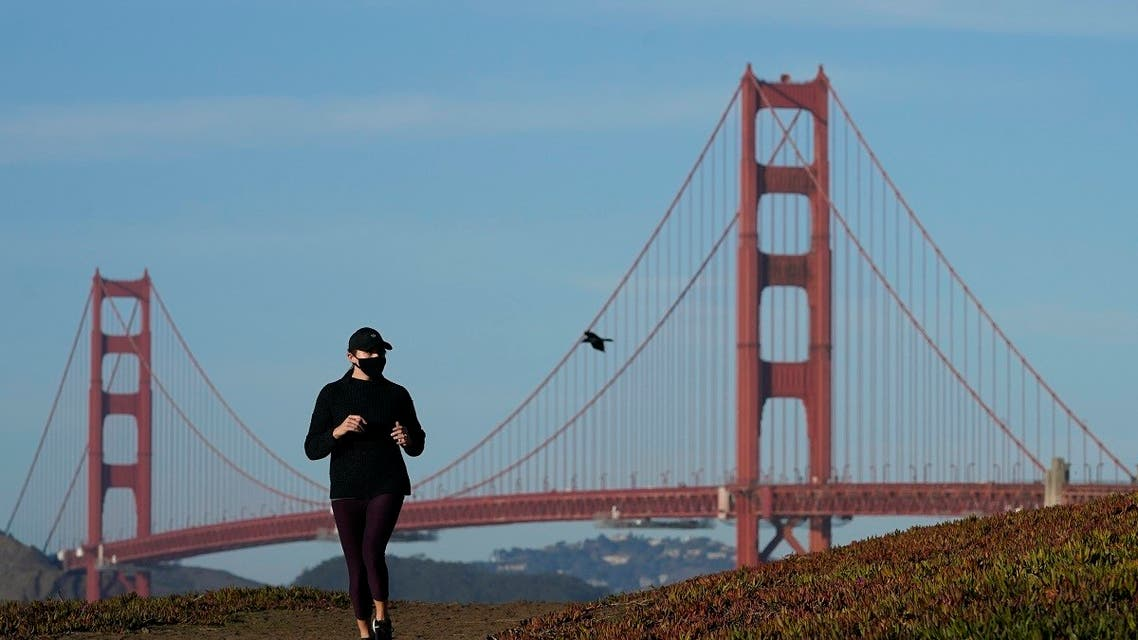 A person wearing a mask runs on a path in front of the Golden Gate Bridge during the coronavirus pandemic in San Francisco. (AP)
