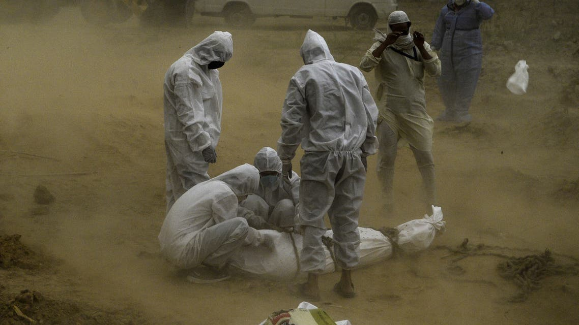 Relatives wearing protective gear tie up the dead body of a victim who died from the COVID-19 coronavirus before the burial at a graveyard in New Delhi on May 10, 2020.