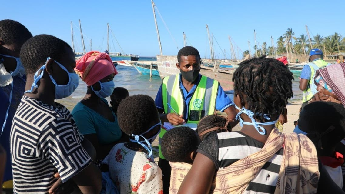 This handout picture taken on November 6, 2020 in Pemba, northern Mozambique, by IOM (International Organization for Migration) shows internally displaced people being assisted by the IOM Displacement Tracking Matrix (DTM) team conducting Emergency Tracking upon their arrival at Pemba's Paquitequete beach by boat. They are counting the number of boats and displaced people who arrived at Paquitequete beach. They record the number of women, men and children and their vulnerabilities (number who are elderly, pregnant, ill). The activity is carried out in close cooperation with Government of Mozambique authorities. The data is used for humanitarian response planning. (Sandra Black/IOM/AFP)